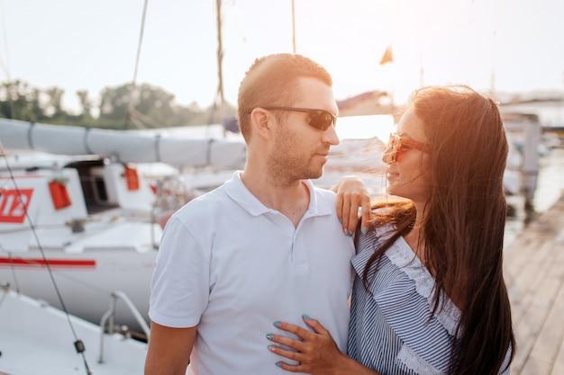 真剣で自信のあるカップルが桟橋に立ち、お互いを見つめる。彼らはサングラスをかけています。人々はとても近くに立っています。彼女は彼の体に手をつないでいます。彼らは白いヨットの近くに立っています。