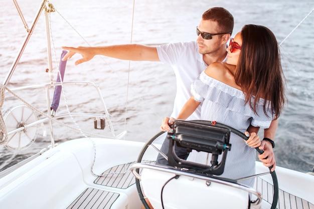 若い人たちが一緒に立って、左を向いている素敵な写真。彼は手で指しています。彼女は舵を握っています。