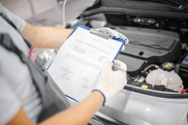 開いた車の車体に立ち、書類を保持する作業員のカットビュー。彼はそれをカメラに見せます