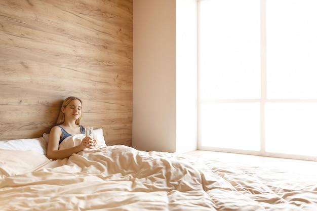 Молодая красивая белокурая женщина лежа в кровати в утре. она держит в руках стакан воды. глаза закрыты с улыбкой на лице. красота утра.