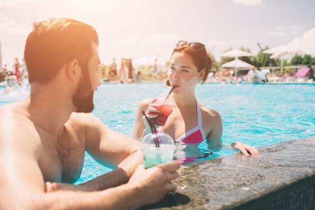 スイミングプールで若いカップル。水でカクテルを飲む男性と女性