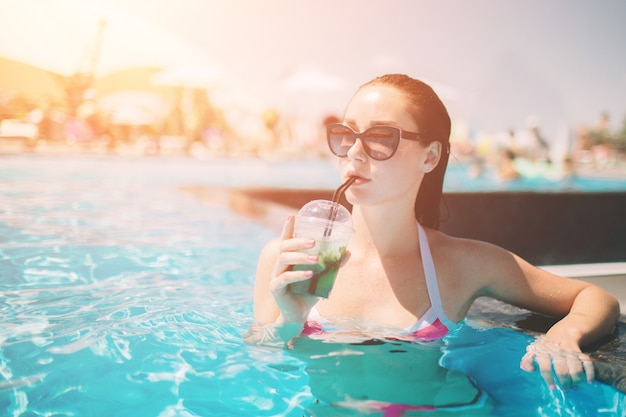 Брюнетка девушка с коктейлями отдыха в бассейне. женщина в бикини, наслаждаясь летним солнцем и загара во время каникул в бассейне с напитком.