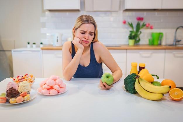 Борьба за диету. молодая грустная женщина в синей футболке, выбирая между свежие фрукты овощи или сладости на кухне. выбор между здоровой и нездоровой пищей.