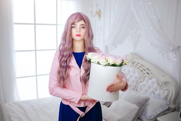 ファッションマニア。グラマーシンセティックガール、空の表情と長いライラックの髪を持つ偽の人形は、白い寝室に立っている間に花のボックスを保持しています。青いドレスのスタイリッシュな美しい女性。美容コンセプト