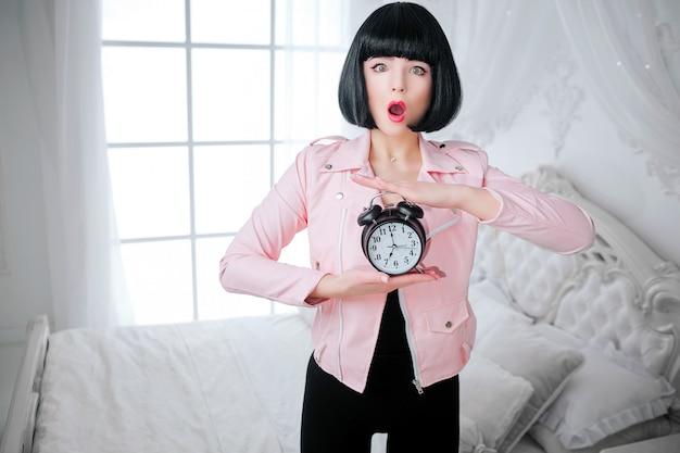 おしゃれなフリーク。短い黒い髪のグラマー感情的な美しい女性は白い寝室に立っている間時計を保持しています。ファッションと美容のコンセプト