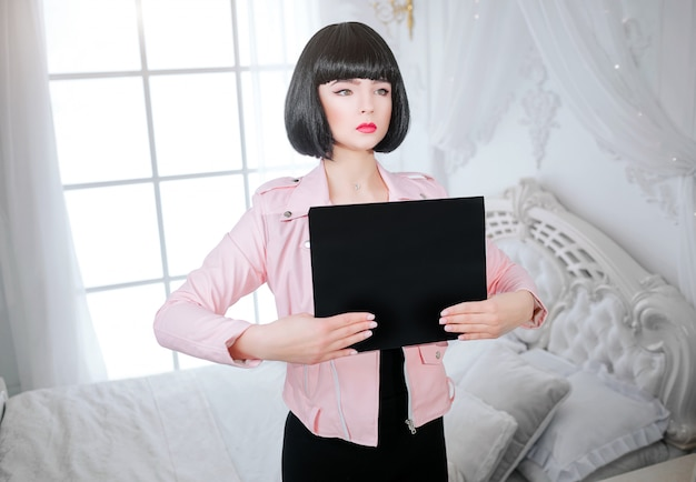 ファッションマニア。ここにあなたのテキスト。グラマーシンセティックガール、短い黒髪の偽の人形が目をそらして、寝室に空の紙を抱えています。ピンクのジャケットでスタイリッシュな女性。