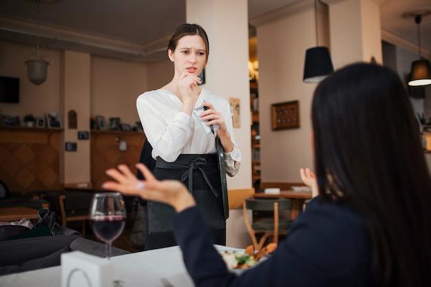 女性客はウェイトレスに文句を言う。