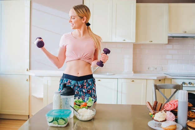 キッチンでエクササイズをしている若いしっかりした造りのスリムなモデル。ダンベルを手に持って見ています。キッチンで一人で。