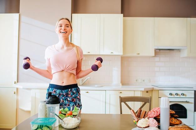 非常に幸せなうれしそうな若い女性の手でダンベルを押しながら運動します。笑顔と幸せに満ちています。キッチンで一人で。