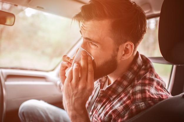 ナプキンでくしゃみをする病気の男の写真。彼はまっすぐ見ています。若い男は苦しんでいます。