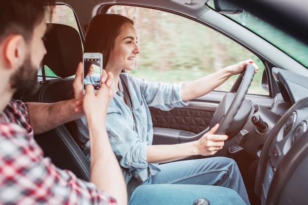 若い男は女の子が車を運転しての写真を撮っています。彼はそれを電話を使ってやっている。女の子は彼女の手でラダーを保持し、まっすぐに見ています。