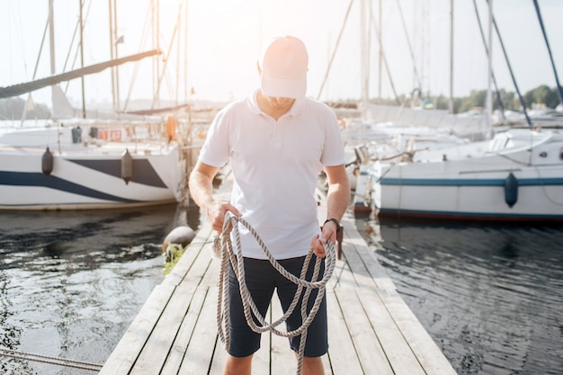 深刻で集中力のある若者の写真。彼は桟橋に立って見下ろしています。男はロープを手に持っています。ヨットの両側にヨットがあります。