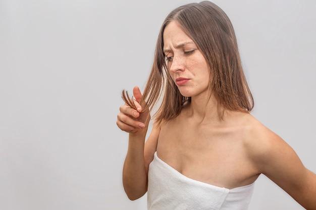 不幸で不満の若い女性が立ち、彼女の髪を見ます。彼女は髪に触れてそれを見ます。女性は彼女の体全体に白いタオルを着ています。