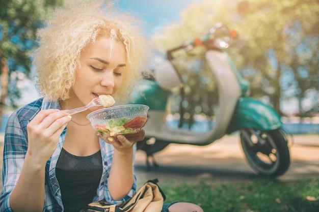 Красивая женщина ест салат
