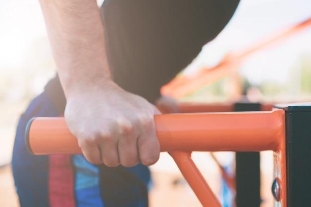 Мускулистый мужчина в черной одежде тренировки делает провалы на брусьях