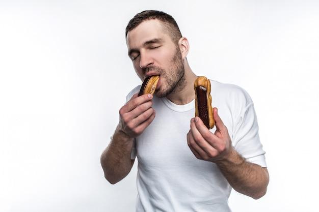 Сильный парень стоит и ест эклер
