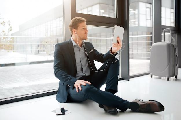 Занят молодой человек сидеть на полу и говорить на планшете