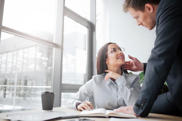 Веселая молодая женщина сидит за столом и улыбается своему боссу