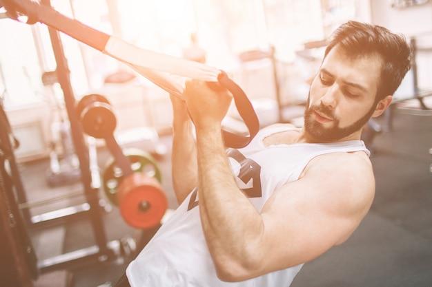 Мускулистый бородатый мужчина во время тренировки в тренажерном зале