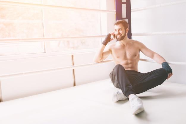 Красивый бородатый боксер с голым торсом тренируется в бойцовском клубе