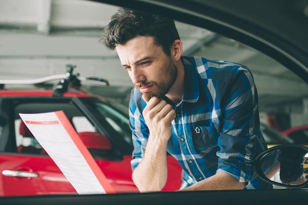 ディーラーで車を調べて彼の選択をする若い黒髪のひげを生やした男。