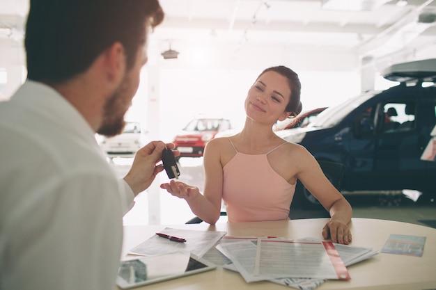 若い女性と話し、ショールームの中で新しい車を見せてフレンドリーな車のセールスマン
