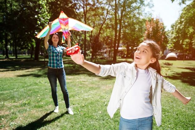 彼女のお母さんと凧で遊ぶ女の子。