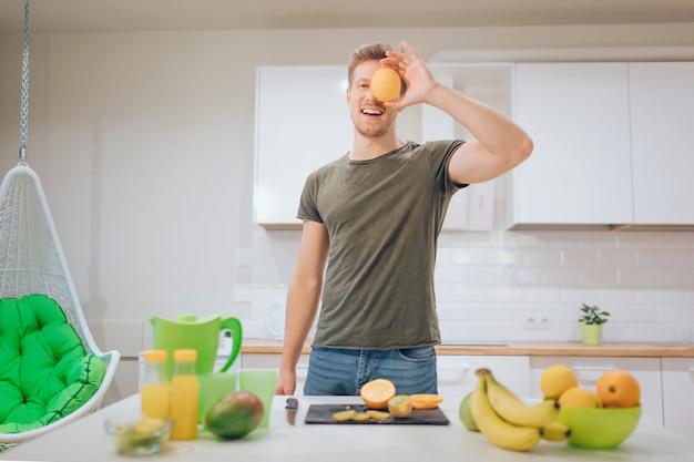 若い笑顔のハンサムな男は、キッチンで新鮮な果物を調理している間に顔の前で甘いオレンジを保持しています。
