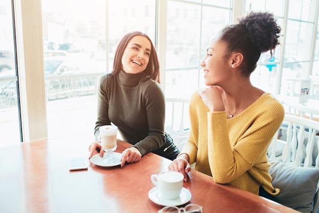 Два лучших друга сидят в кафе и хорошо проводят время вместе. девушки пьют латте и наслаждаются разговором.