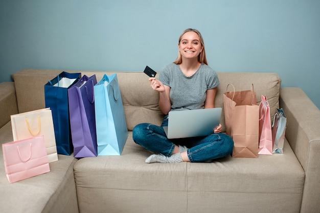 いくつかの買い物袋が付いているソファーに座っているクレジットカードを持つ若い幸せな女
