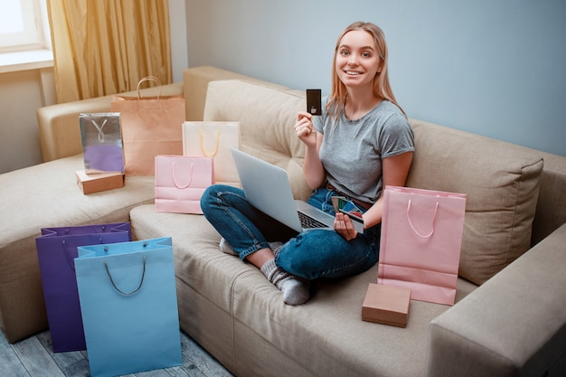 クレジットカードを持つ若い幸せな買い物客は買い物袋が付いているソファーに座っている間最高の販売を選択しています