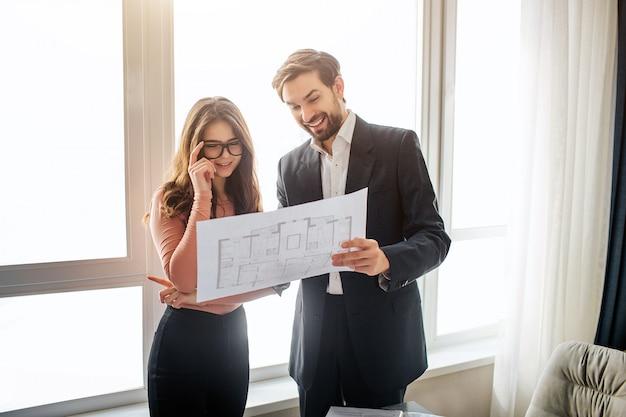 メガネの若い女性は計画と笑顔を見てください。陽気な男がそれを指しています。窓際に立っています。明け。
