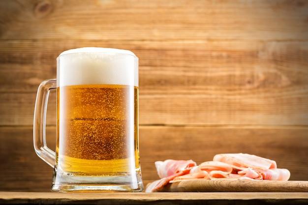 Стекло с пивом на деревянной стене.