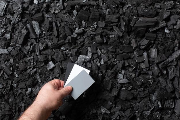 Древесный уголь фон. рука держит серую карту для установки баланса белого. черная текстура