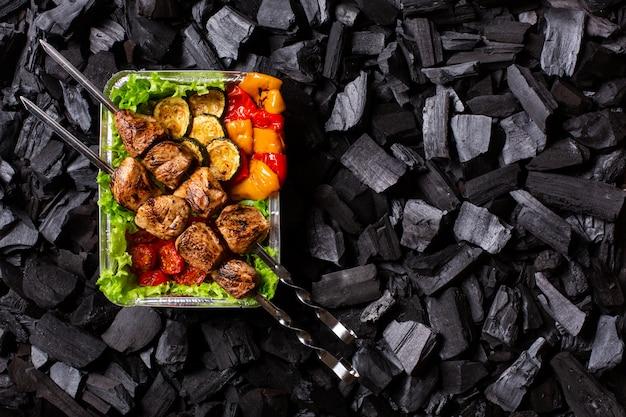 Готовый шашлык. часть жареного мяса и овощей в одноразовой таре на фоне древесного угля. копировать пространство