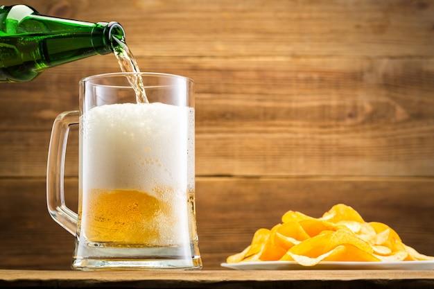 Заполнение стакан с пивом на деревянной стене.