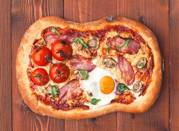 Свежая вкусная пицца из духовки с яйцом, прошутто и помидором