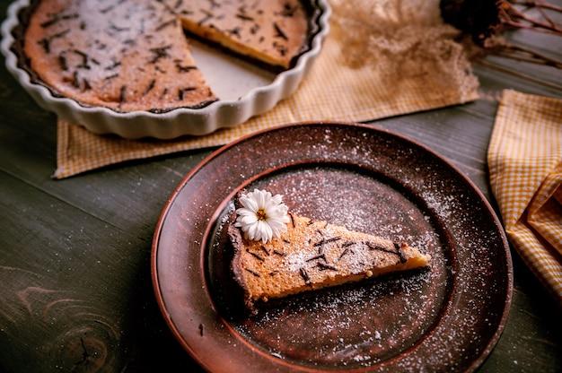 木製のテーブルの上にチョコレートスライスを振りかけたセラミックフォームで焼いたケーキ。粘土板に置かれ、花で飾られたケーキのスライス