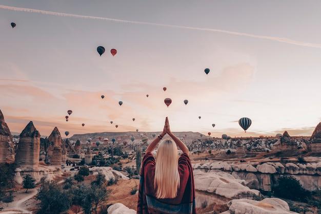 たくさんの風船が愛の谷の上を飛ぶ飛行を見ている夜明けの民族衣装の女の子