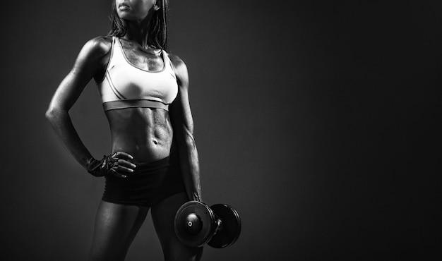 Афро-американская девушка фитнес-тренер с гантелями, делая упражнения