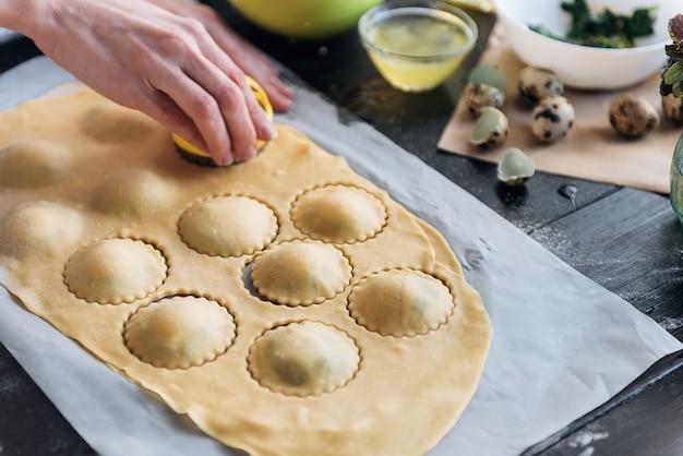 Шаг за шагом шеф-повар готовит равиоли с сыром рикотта, желтками перепелиных яиц и шпинатом со специями. шеф-повар создает равиоли