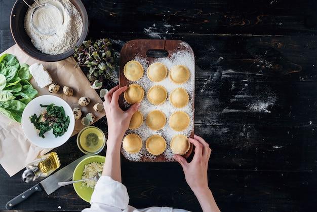 Шаг за шагом шеф-повар готовит равиоли с сыром рикотта, желтками перепелиных яиц и шпинатом со специями. шеф-повар готовит готовить равиоли