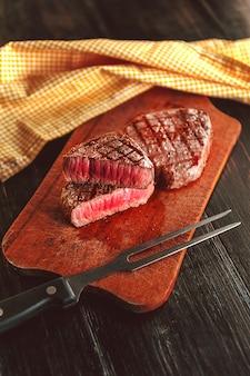 暗い木製の表面にフォークでステーキ