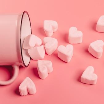 Розовая кружка лежит на боку на розовой поверхности, из нее посыпаны светло-розовые зефиры в форме сердечек.