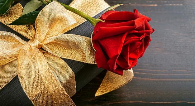 Подарок, завернутый в черную бумагу и золотую ленту. сверху коробки лежит роскошная красная роза.