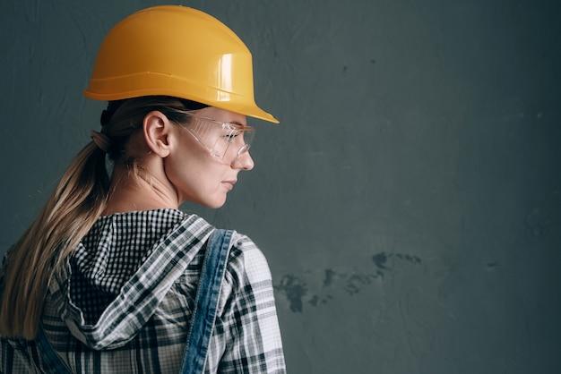 建設用ヘルメット、ミトン、ゴーグル、オーバーオールを着た意欲的な女性が自宅で修理と建設作業に従事しています。強くて自立した女性の概念