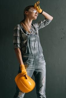 Работница в шлеме устала и вытирает пот со лба