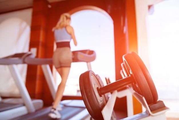 Девушка с утра бегает по беговой дорожке в спортзале перед большим окном на фоне моря