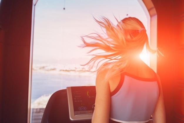 朝の少女は、海の背景に大きな窓の前にジムでトレッドミルで実行