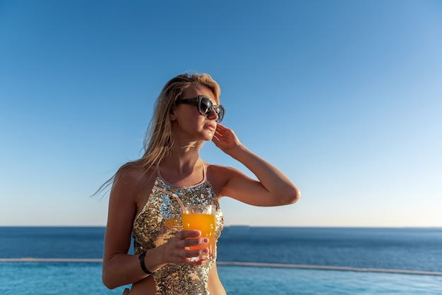 彼女の手でカクテルと高価な水着の女の子は、リゾートのプールの近くで彼女の休暇を過ごす